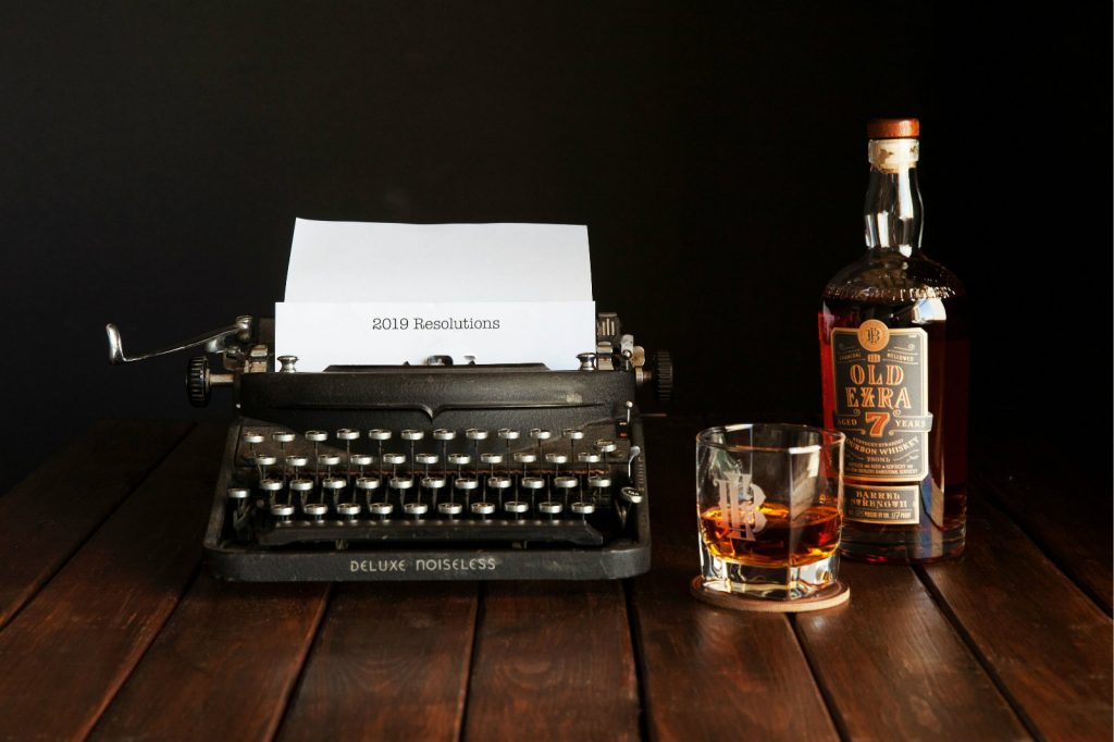 A bottle of Old Ezra and a glass of bourbon sitting next to a typewriter